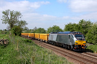 DRS 68013 in silver Chiltern Railways Livery is seen at the foot crossing west of Narborough Station on 15.5.15 with 6U76 0859 Crewe Bas Hall S.S.M. - Mountsorrel Sdgs empty yellow Network Rail IOA wa
