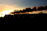 LMS Ivatt Class 2 2-6-0 No 46521 is silhouetted against  the setting sun approaching the signal at Quorn on 29.12.14 with 1515 Loughborough - Leicester North GCR Christmas Holiday Service