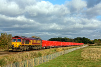 DB Cargo UK 66100  passes Rearsby west of Melton Mowbray on 5.11.16 with a rake of red DB MMA open box wagons contrasting against the dark clouds with 6Z90 0822 Middleton Towers - Arpley Sidings  sand