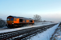 The low sun glints on 66715 at a snowy Cossington, MML on 22.12.10 with 4E80 1311 Hotchley Hill (East Leake) - West Burton Power Station empty gypsum containers