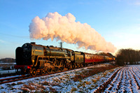 BR Standard Class 7 No 70013 'Oliver Cromwell' catches the low sun turning the steam pink at a snowy Quorn on 28.12.14 with 1500 Leicester North - Loughborough GCR Christmas Holiday Service