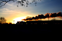 LMS Ivatt Class 2 2-6-0 No 46521 is silhouetted against  the setting sun at a snowy Quorn on 29.12.14 with 1515 Loughborough - Leicester North GCR Christmas Holiday Service