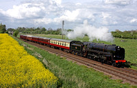 British Railways Standard Class 9F 2-10-0 No.92214 at Woodthorpe alongside a yellow oil rapeseed field on 26.4.14 with 1615 Loughborough - Leicester North GCR service