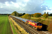 With the Autumn colours just about hanging on at Barrow Upon Trent, DB Cargo Uk 66082 passes a Network Rail gang on 10.11.16 with 6E54 1035 Kingsbury Oil Sdgs - Humber Oil Refinery empty blue bogie ta